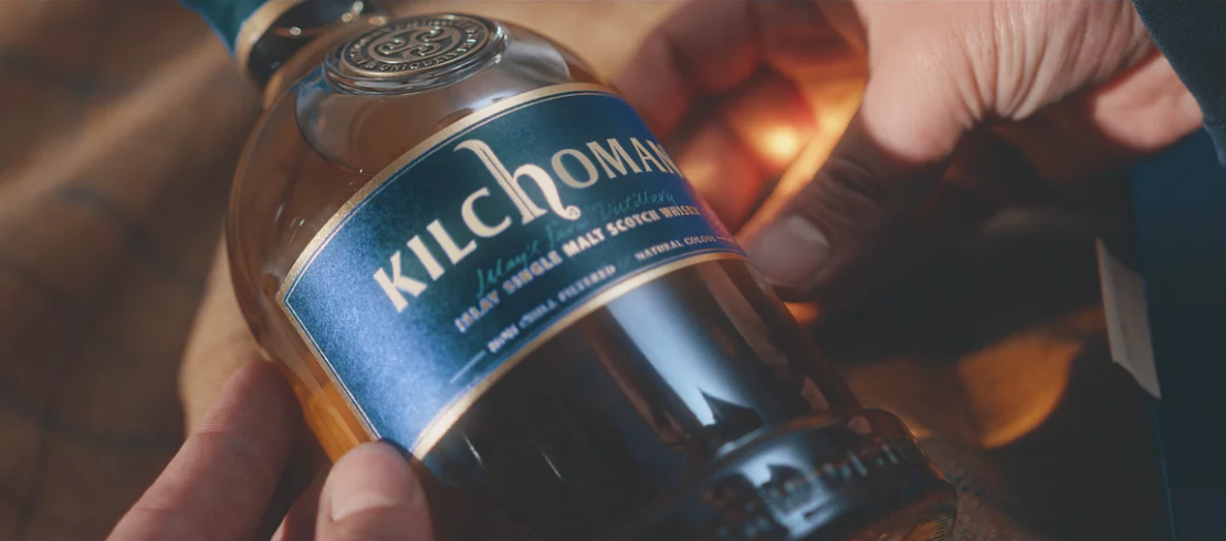 Man admiring a bottle of Kilchoman 30 year old whisky.